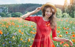 Lovely young romantic woman in straw hat on poppy flower...