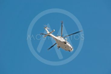 Helicopter flying overhead in a blue sky.