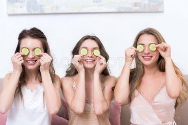 beautiful smiling young women in pajamas holding cucumber...