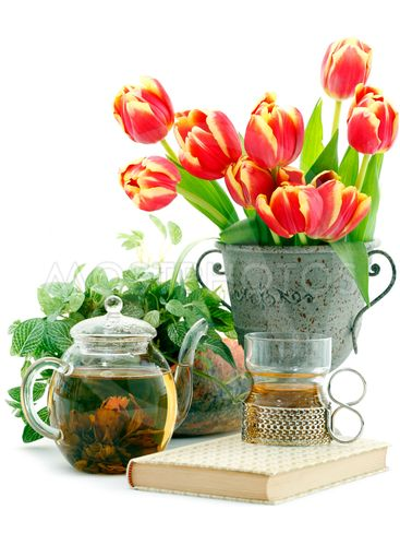 tea in tea glass and pot, book and bunch of tulips in old...