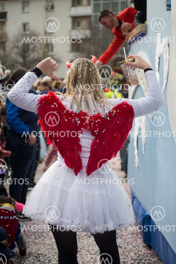 girl parading in the street with angel costume and red...