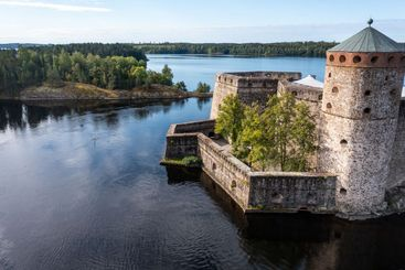 Walls of a medieval Stone castle and lake in summer