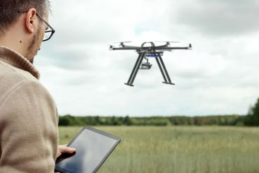 A male farmer manages a drone over agricultural land....