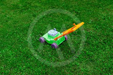 Children's toy lawn mower is on the grass