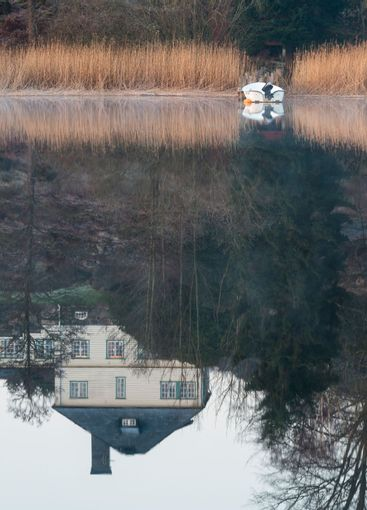 Reflection of house in idyllic lake. Rådasjön, Sweden