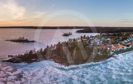 Solnedgång på vintern över isbelagd sjö drönare