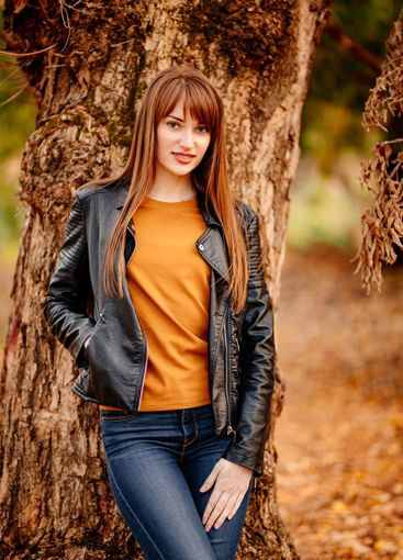 beautiful woman near tree in autumn Park.