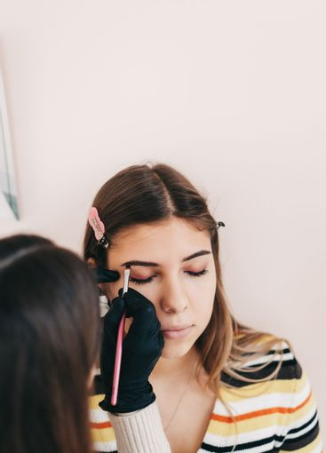 Eyebrow shaping procedure, make-up master uses brush to...