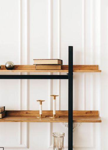 Decorative wooden shelves in living room with books and...