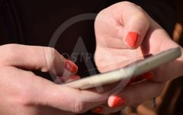 A woman sends messages with the mobile phone