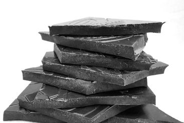 Pieces of dark, inferior chocolate in black and white