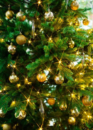artificial Christmas tree decorated with gold toys and...