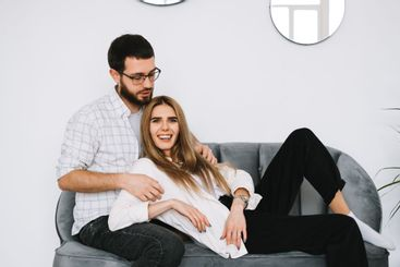Young happy couple embrace and resting on a sofa at home.