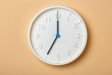 white wall clock with blue second hand