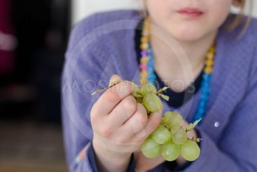 Girl holding grapes