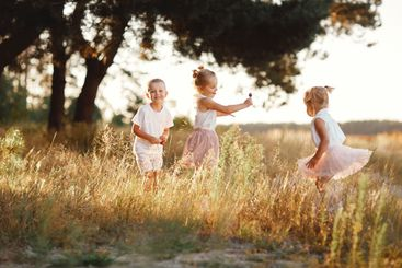 three children playing in the field in summer. young...