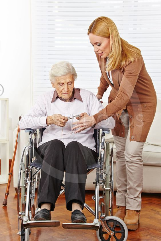 Woman giving glasses to senior citizen in wheelchair