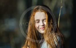 Long-haired skinny girl in a summer pine forest.
