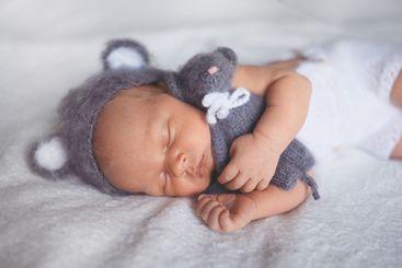 Cute emotional newborn little baby boy sleeping in crib...
