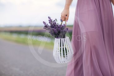 Beautiful young woman in blue dress holds bouquet of...