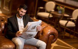 Modern businessman reading newspapers
