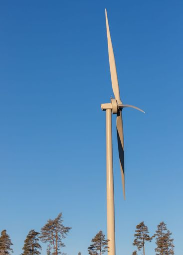 Huge wind mill against clear blue sky background.
