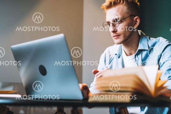 Caucasian man college student in glasses studying with...