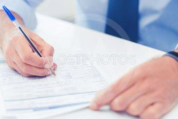 man filling tax form