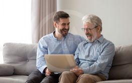 Smiling grown son and senior dad laugh using laptop...