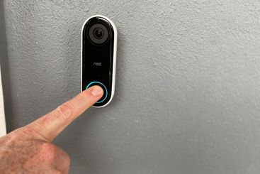 A person pressing a Ring doorbell