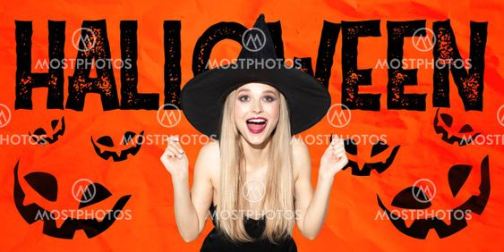 Young woman in hat as a witch on scary red background