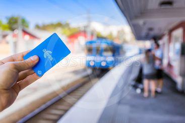 En hand håller upp ett SL Access-kort, med tåg och...