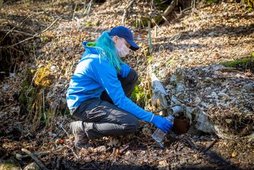 Ecologist taking water samples from a natural source in...