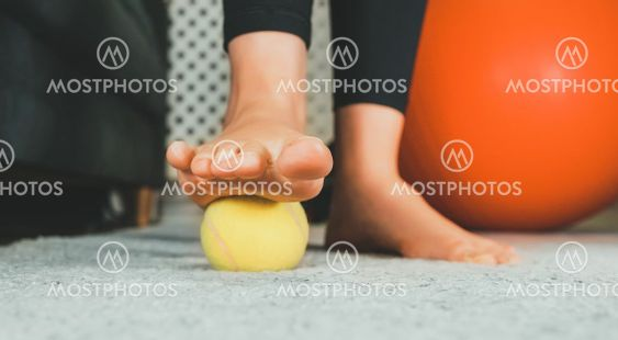 Woman massaging her foot with tennis ball.