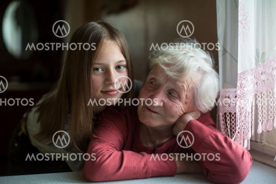 Little girl hugging elderly grandmother for a photo.