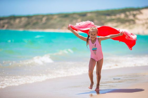Little girl have fun with beach towel during tropical...
