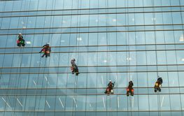 group of workers cleaning windows service on high rise...