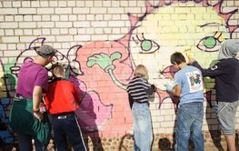 children paint graffiti on the wall