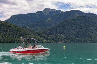 Family sailing in speedboat at Wolfgangsee near Sankt...