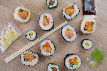 Sushi set of maki with chopsticks and various sauces