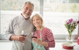 Smiling senior couple holding glass of wine in kitchen