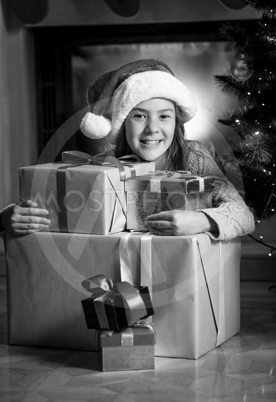 portrait of cute smiling girl posing with Christmas gift...