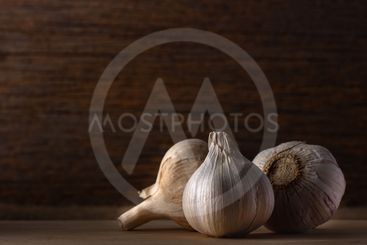 group of garlic head on wooden background , low light.