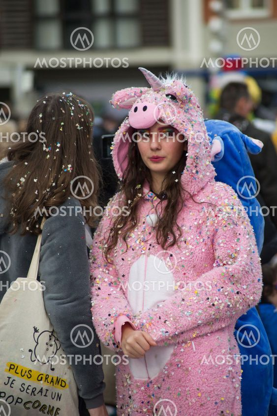 girl wearing a unicorn costume in the street during the...