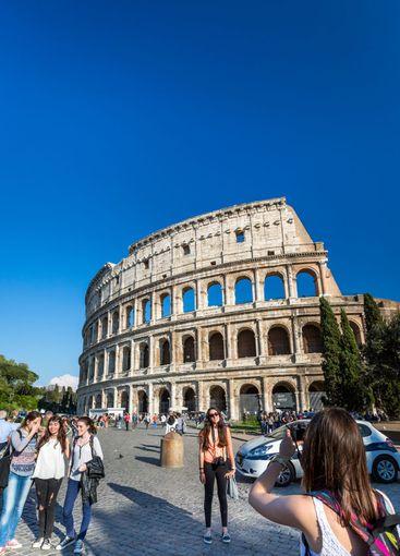 Unga kvinnliga turister framför Colosseum i Rom.