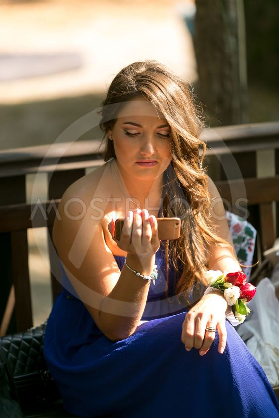 brunette bridesmaid using smartphone and browsing internet