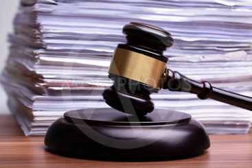 Judge Gavel In Front Of Stacked Files On Table