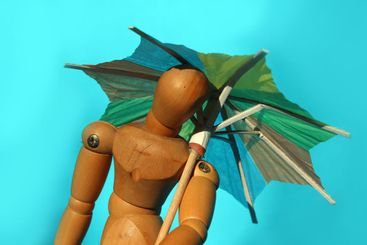 Close up of wooden mannequin with colored beach umbrella