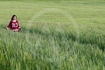 Young teenage girl walking on a wheat field
