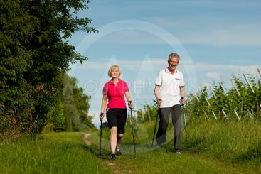 Happy mature or senior couple doing Nordic walking in...